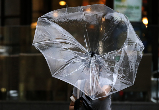 A woman struggles with an umbrella in strong winds and rain caused by Typhoon Halong in Tokyo