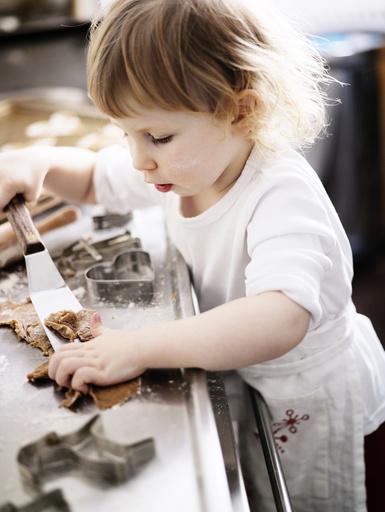 A little girl baking gingerbread, Sweden.