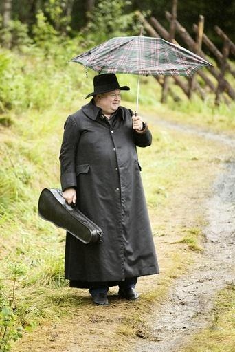 Knut Buen med sort skinnfrakk og paraply under øving til Marispelet. Teater, Sogelandet, Marispelet, Rjukan