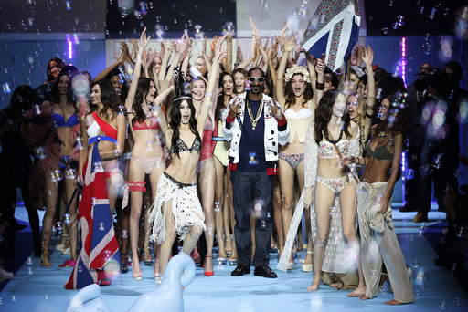 US rapper Snoop Lion, known as Snoop Dogg performs next to models during the Etam Live Show Lingerie at Piscine Molitor during Paris Fashion Week