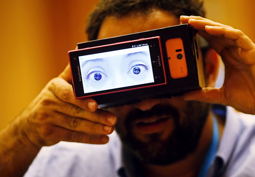 File photo of a visitor trying on Truth goggles during a design competition showcase of wearable technology in Singapore