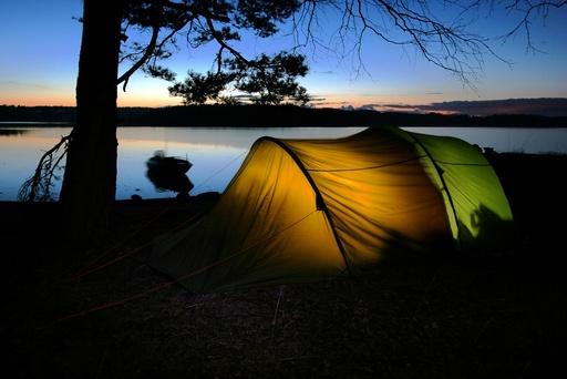 Telt i skjærgården. Sommernatt med vindstille hav og lys himmel. Fjelltelt, tunneltelt.