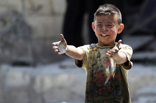A boy, whose brother was killed, reacts at site hit by airstrikes in rebel-controlled area of Maaret al-Numan town in Idlib province