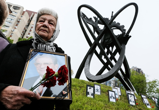 A woman holds a portrait of her relative, a victim of the Chernobyl nuclear disaster, during a ceremony in Kiev