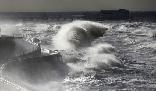 Waves break in front of the South Pier on Blackpool Promenade, northern Britain