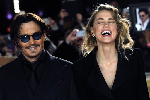 Actor Johnny Depp and girlfriend Amber Heard laugh as they arrive for the UK premiere of