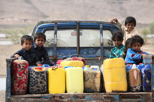 Children ride on the back of a truck loaded with water jerrycans at a camp for internally displaced people in the Dhanah area of the central province of Marib, Yemen