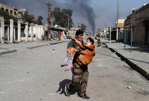An Iraqi special forces soldier carries a woman injured during a battle between Iraqi forces and Islamic State fighters in Mosul