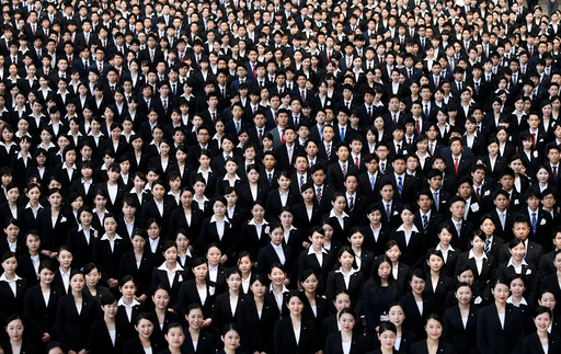 Newly-hired employees of JAL group pose for photos during an initiation ceremony at a hangar of Haneda airport in Tokyo