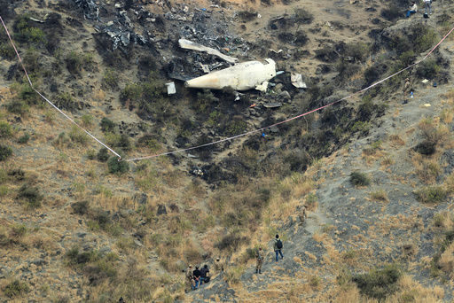 Rescue workers survey the site of a plane crashed a day earlier near the village of Saddha Batolni, near Abbotabad, Pakistan