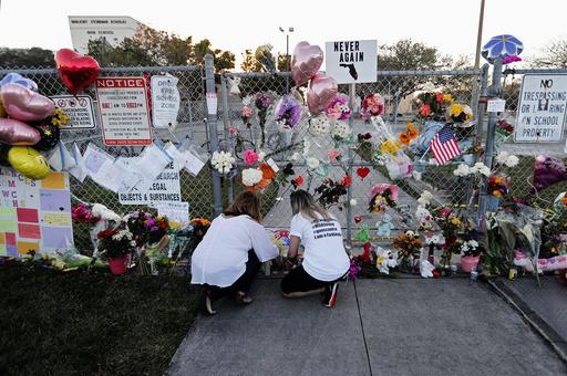 Folk legger ned blomster for å minnes ofrene etter skoleskytingen i Parkland i Florida i februar 2018. Tre år etter skoleskytingen ber USAs president Joe Biden Kongressen godkjenne våpenreformer. Foto: Gerald Herbert / AP / NTB