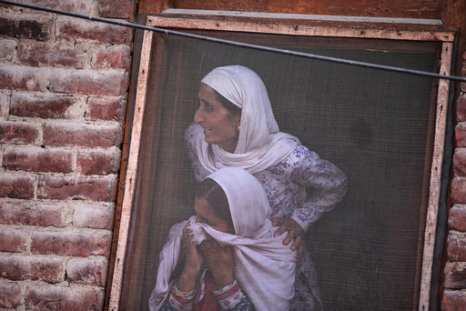 Kashmiri women watch the funeral of Muzaffar Ahmad Pandit, a civilian, who according to local media succumbed to injuries from pellets fired by Indian police during clashes earlier this month in Budgam