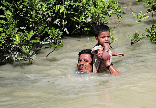 A Rohingya refugee man hols his child as he swims to cross Myanmar-Bangladesh border in Palang Khali
