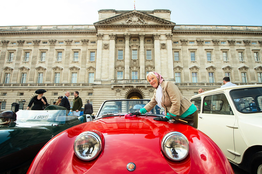 Carole Clark polishes a 1958 Austin Healey Sprite mk1, part of a display of 90 historic British-built motor vehicles standing on the forecourt of Buckingham Palace commemorating Queen Elizabeth's 90th birthday, in London