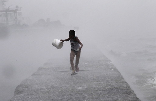 A boy runs as heavy rains and high waves brought by typhoon Linfa, locally named Egay, crash along a breakwater along Manila Bay at a slum area in Baseco, Tondo in Manila
