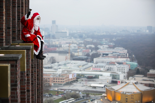 A man dressed as a Santa Claus poses at the front of the Kollhoff Tower at Potsdamer Platz square in Berlin