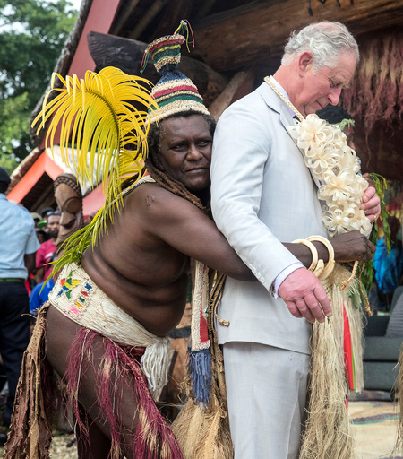 Britain's Prince Charles is given a grass skirt to wear prior to receiving a chiefly title during a visit to the Chiefs' nakamal, as he visits the South Pacific island of Vanuatu