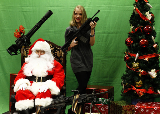 A woman holds an automatic weapon as she poses for a picture with a man dressed as Santa Claus at the Scottsdale Gun Club in Scottsdale