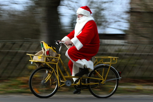 A man dressed as Father Christmas rides a bicycle in the village of Himmelpfort