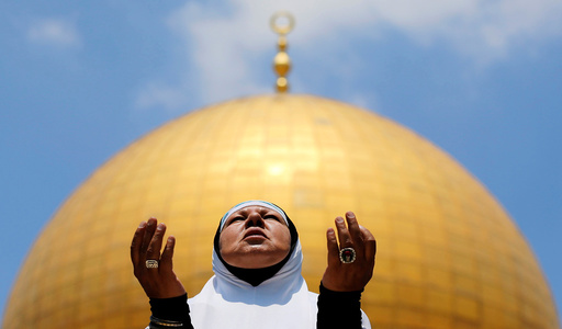 A Palestinian woman prays on the first Friday of the holy fasting month of Ramadan, on the compound known to Muslims as Noble Sanctuary and to Jews as Temple Mount, in Jerusalem's Old City