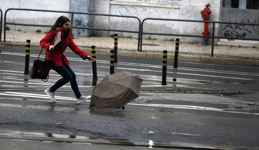 A woman tries to catch her umbrella after it was blown away by the wind in downtown Lisbon