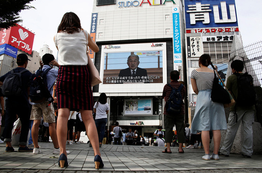 People watch a large screen showing Japanese Emperor Akihito's video address in Tokyo