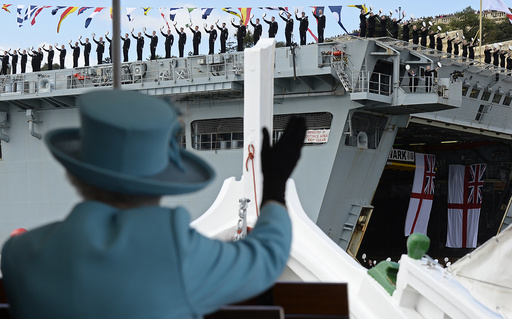 Britain's Queen Elizabeth waves to British Royal Navy crew members performing a salute on the HMS Bulwark amphibious assault ship during a State Visit and Commonwealth Heads of Government Meeting in Valletta