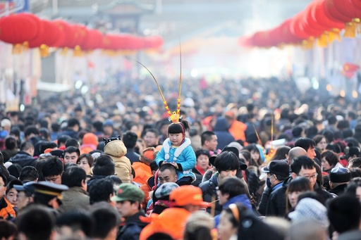 A girl wears a monkey king headwear at a festival fair during Chinese Lunar New Year celebrations in Qingdao