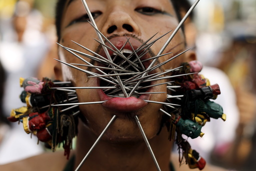 A devotee of the Chinese Samkong Shrine walks with spikes pierced through his cheeks during a procession celebrating the annual vegetarian festival in Phuket, Thailand