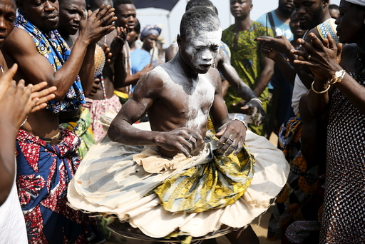 A devotee is cheered as he dances at the annual voodoo festival in Ouidah