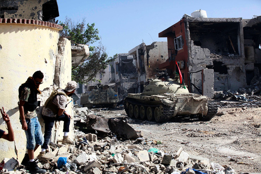 Fighters of Libyan forces allied with the U.N.-backed government take cover during a battle with Islamic State militants in Ghiza Bahriya district in Sirte