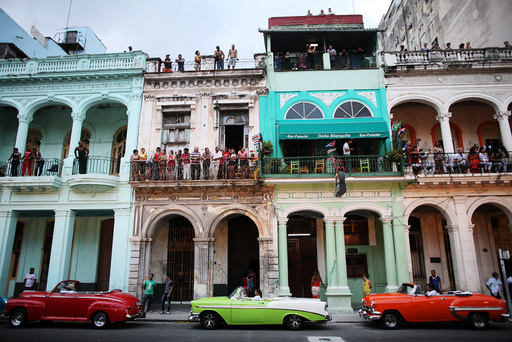 People stand on balconies prior to a fashion show displaying creations by German designer Karl Lagerfeld as part of his latest inter-seasonal Cruise collection for fashion house Chanel at the Paseo del Prado street in Havana, Cuba