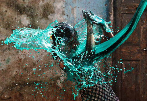 A girl reacts as coloured water is thrown on her face while celebrating Holi, the Festival of Colours, in Mumbai