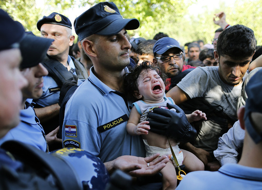 A Croatian policeman holds a crying baby as he stands among migrants waiting to board a bus in Tovarnik