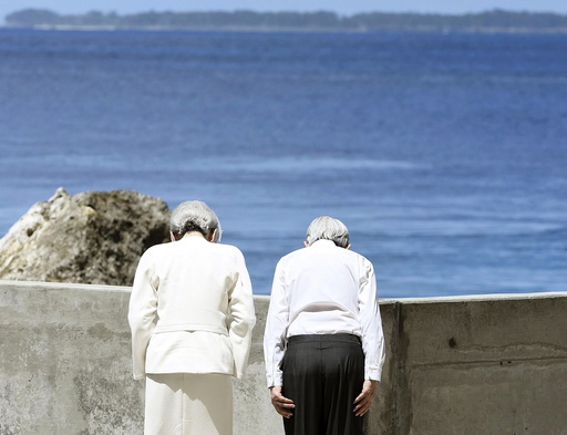 Japan's Emperor Akihito and Empress Michiko bow towards Angaur Island after they offered flowers to the cenotaph for war dead in the western Pacific area, on Palau's Peleliu Island