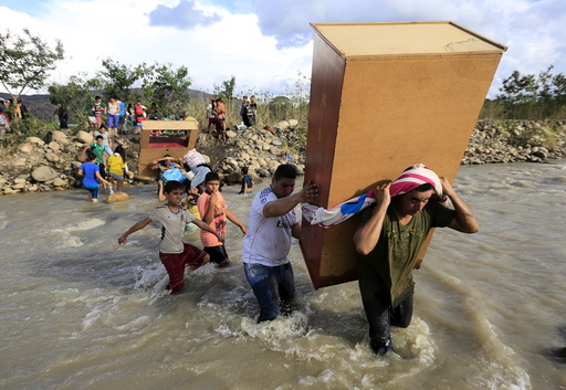 People carry their belongings while crossing the Tachira river border with Venezuela into Colombia near Villa del Rosario village