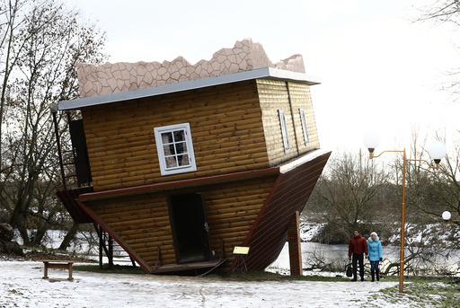 People walk outside an upside-down house in a tourist complex, near the village of Dukora