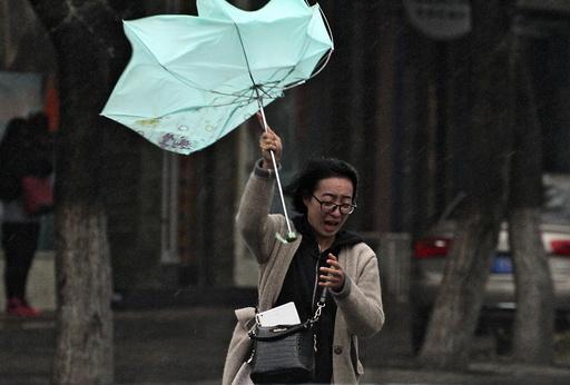 A woman's umbrella is blown by wind during a heavy rain in Yantai