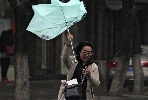 A woman's umbrella is blown by wind during a heavy rain in Yantai