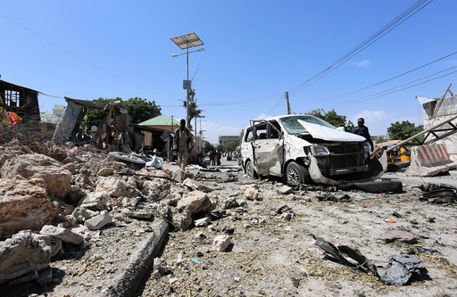 Somali policemen attend scene of a suicide attack outside the main base of an African Union peacekeeping force in Mogadishu