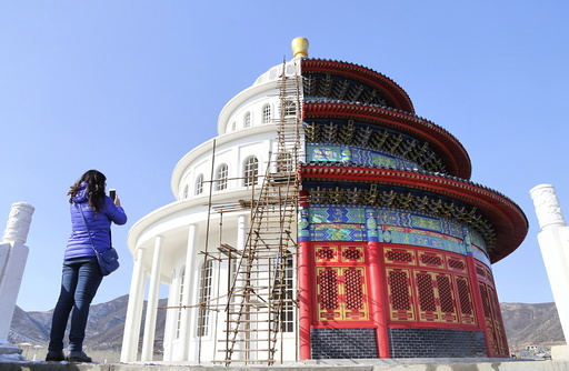 Woman takes pictures at a building, which is made by half of a replica of the Qinian Hall of the Temple of the Heaven and half of a western building, at a studio for productions of films and television shows on the outskirts of Shijiazhuang