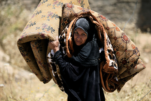 A displaced Iraqi woman who fled her home carries a mattress in al-Zanjili neighbourhood