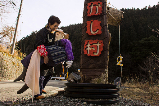 Tsukimi Ayano carries a scarecrow to place it on the road leading into the mountain village of Nagoro