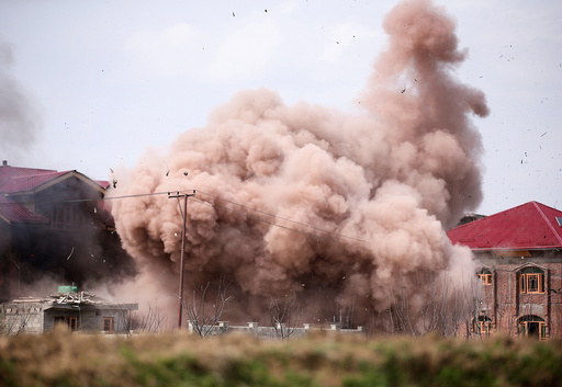 Clouds of smoke and dust billow as a residential house is blown up during a gunbattle between Indian soldiers and suspected militants in Chadoora
