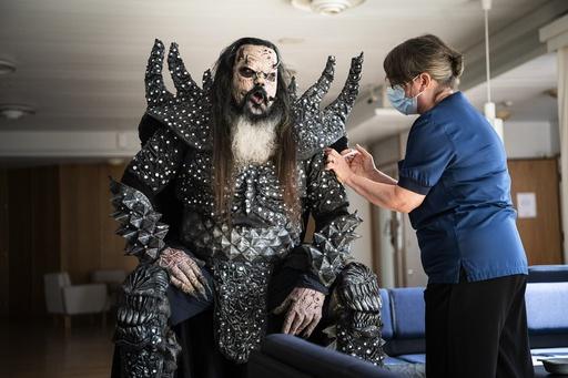 Mr Lordi i det finske bandet Lordi får andre dose koronavaksine av sykepleier Paula Ylitalo i Rovaniemi i Nord-Finland. Foto: Jouni Porsanger / Lehtikuva via AP / NTB