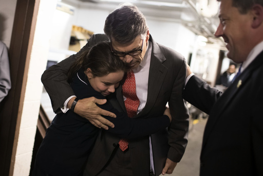 Rick Perry, the former governor of Texas, gets a hug from Madeline Martin, whose father leads the conservative interest group Perry was to address in St. Louis.