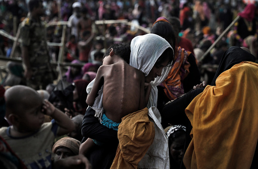 A woman carries her ill child in a refugee camp at Cox's Bazar