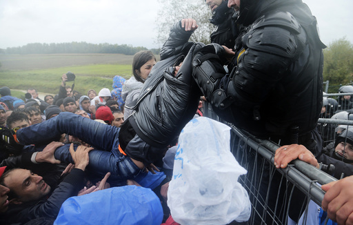 A man is lifted over a fence by Slovenian policemen as migrants attempt to cross the border near Trnovec