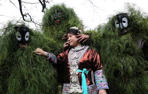 Ethnic Miao men wearing traditional masks smear dust on a woman's face to wish her good luck during a local celebration event for Lunar New Year in Liuzhou