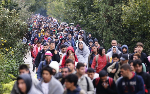 Migrants walk to the Austrian border in Nickelsdorf from Hegyeshalom